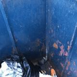 Il sort de l'église et voit quelque chose au fond d'une poubelle : en se penchant, il comprend qu'il doit appeler la police