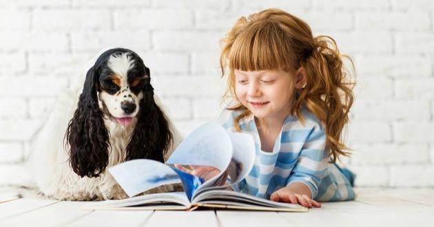 un chien et une petite fille qui lit