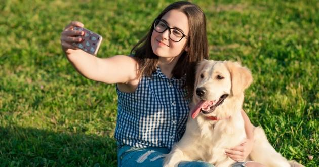 une jeune femme qui prend un selfie avec son chien