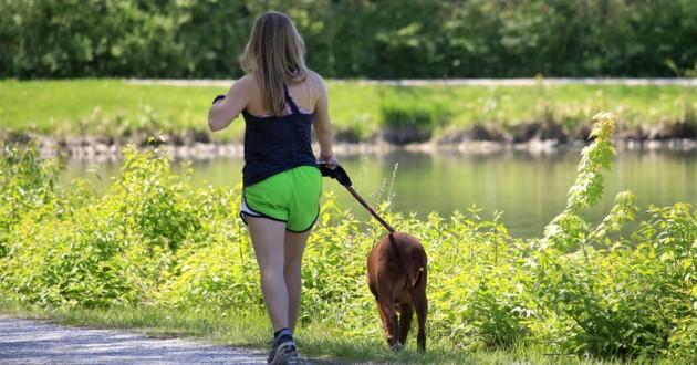 femme qui se promène avec son chien près d'un lac