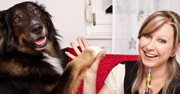 femme qui fume une e cigarette à coté de son chien