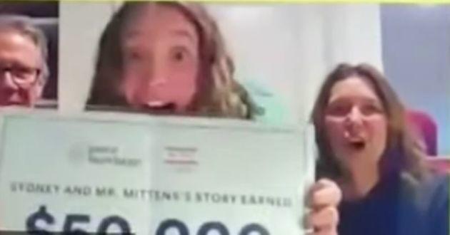 Sidney affichant son chèque de 50 000 dollars