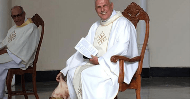 Le prêtre caressant le chien