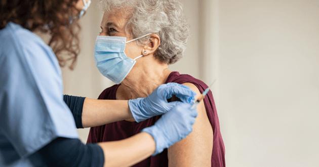 Gros plan sur une aiguille dans un flacon de vaccin contre le Covid