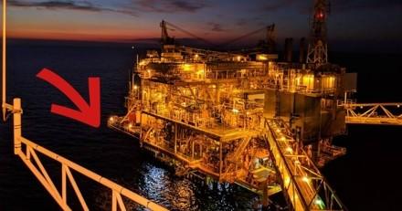 Sur une plateforme pétrolière, un ouvrier voit une ombre dans l'eau et se met à courir dans tous les sens